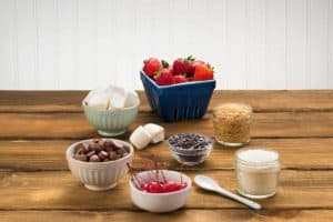 Bowls of marshmallows, chocolate, cherries, strawberries, coconut and sugar on brown table