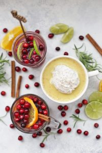 Superfood Holiday Drinks with cinnamon sticks, fruit and herbs laying around the glasses