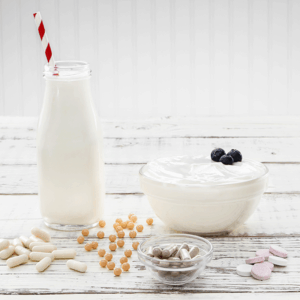 Bottle of milk with straw, bowl of yogurt with blueberries and assorted vitamins on white wood