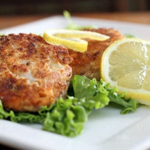 Salmon cakes over green lettuce with lemon slices on a white plate