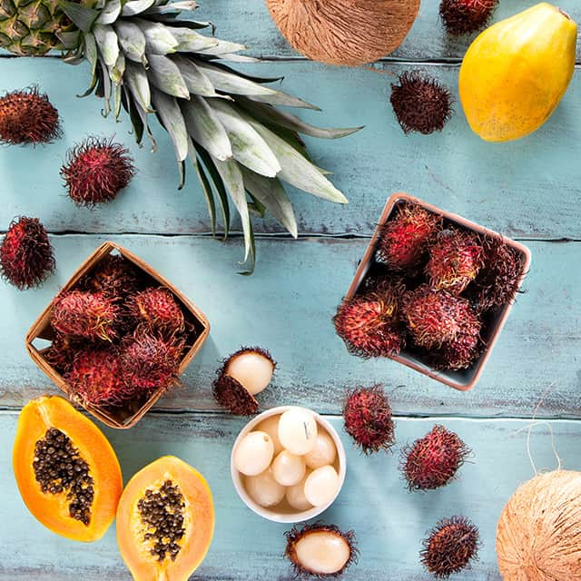 Rambutans and assorted tropical fruits on teal wood