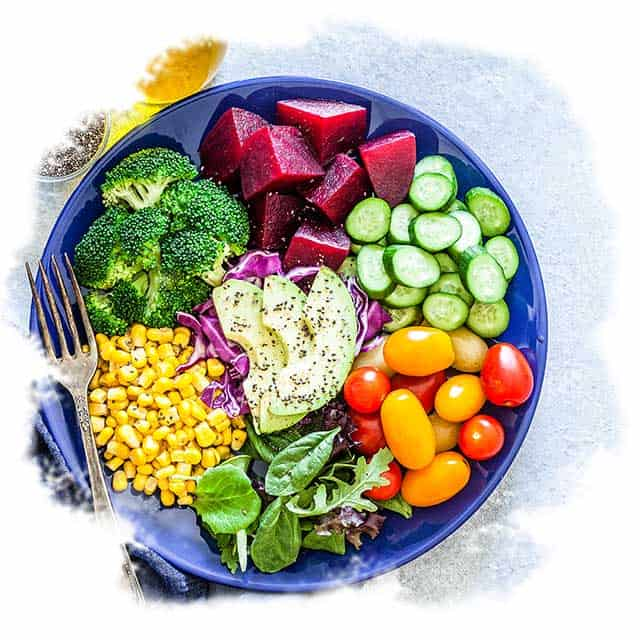 A plate of fresh produce including beets, broccoli, tomatoes and spinach.