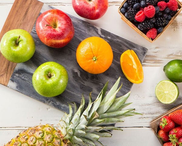 berries, citrus and apples on a cutting board