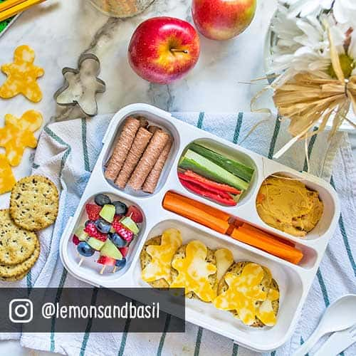 crackers, fruit, vegetables and cheese in a lunch box