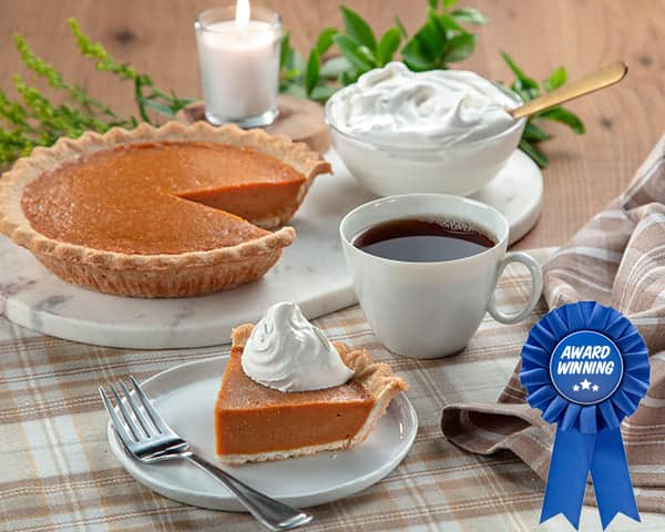 Pumpkin pie, apple pie, pecan pie, and a cup of coffee on festive table